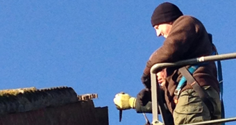An ecologist performing an ecological clerk of works in a cherry picker whilst a roofer strips tiles